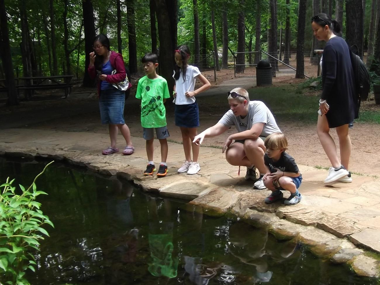 An instructor and family dip netting at the Blue Jay Study Pond