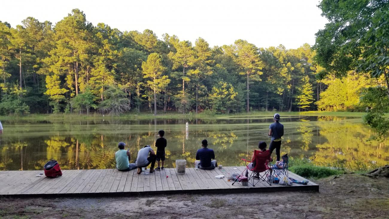 Photo of a family fishing together on the dock located at the Fishing Pond