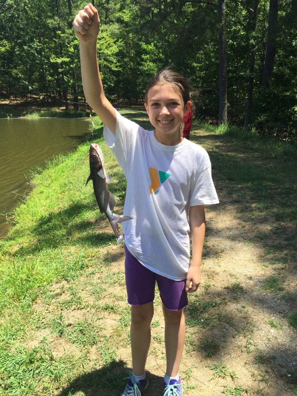 A photo of a female camper holding a catfish she just caught