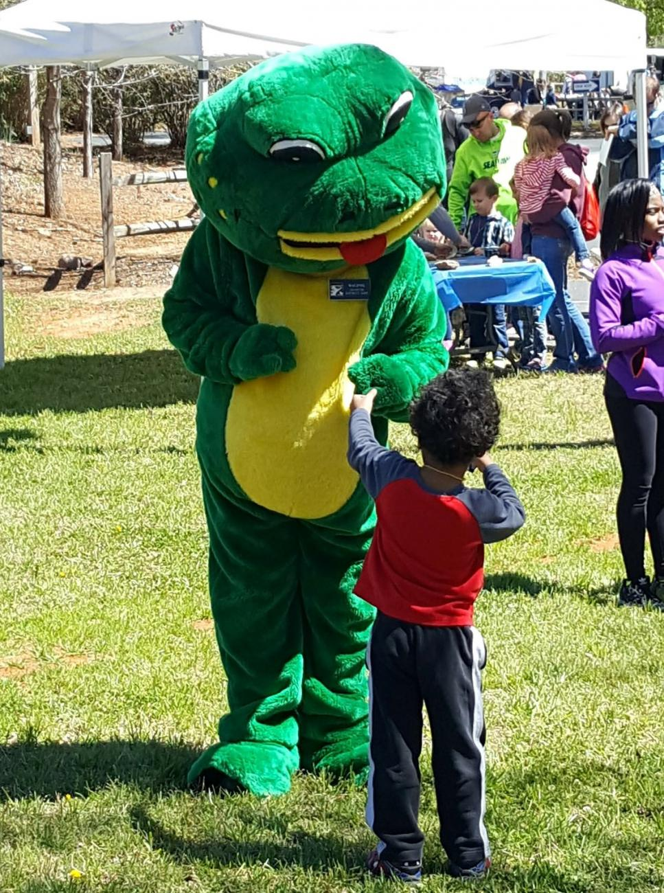 frog mascot stands with child on open play field with tents and trees in background