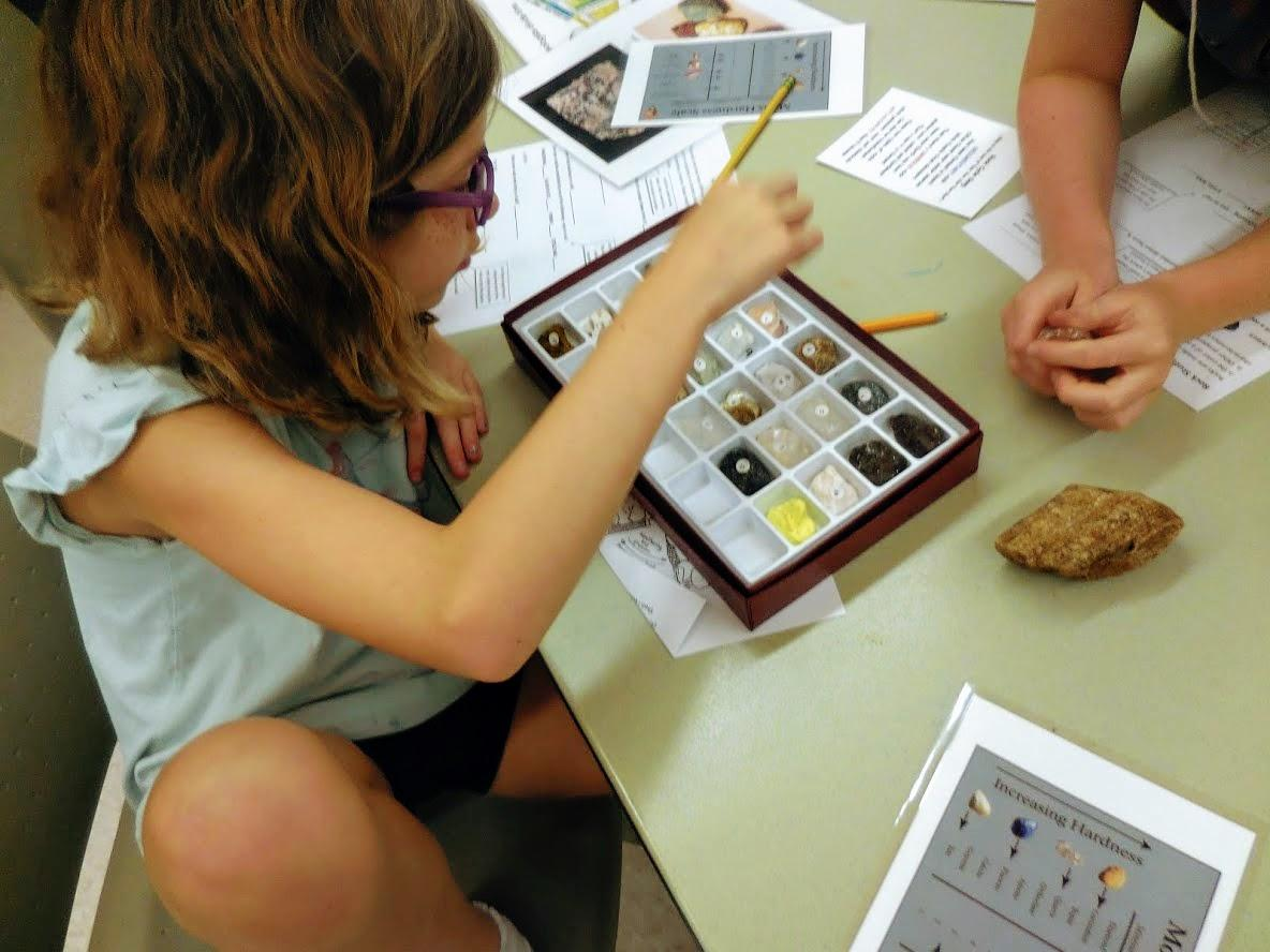child sits at table with rock set and worksheet during field school program