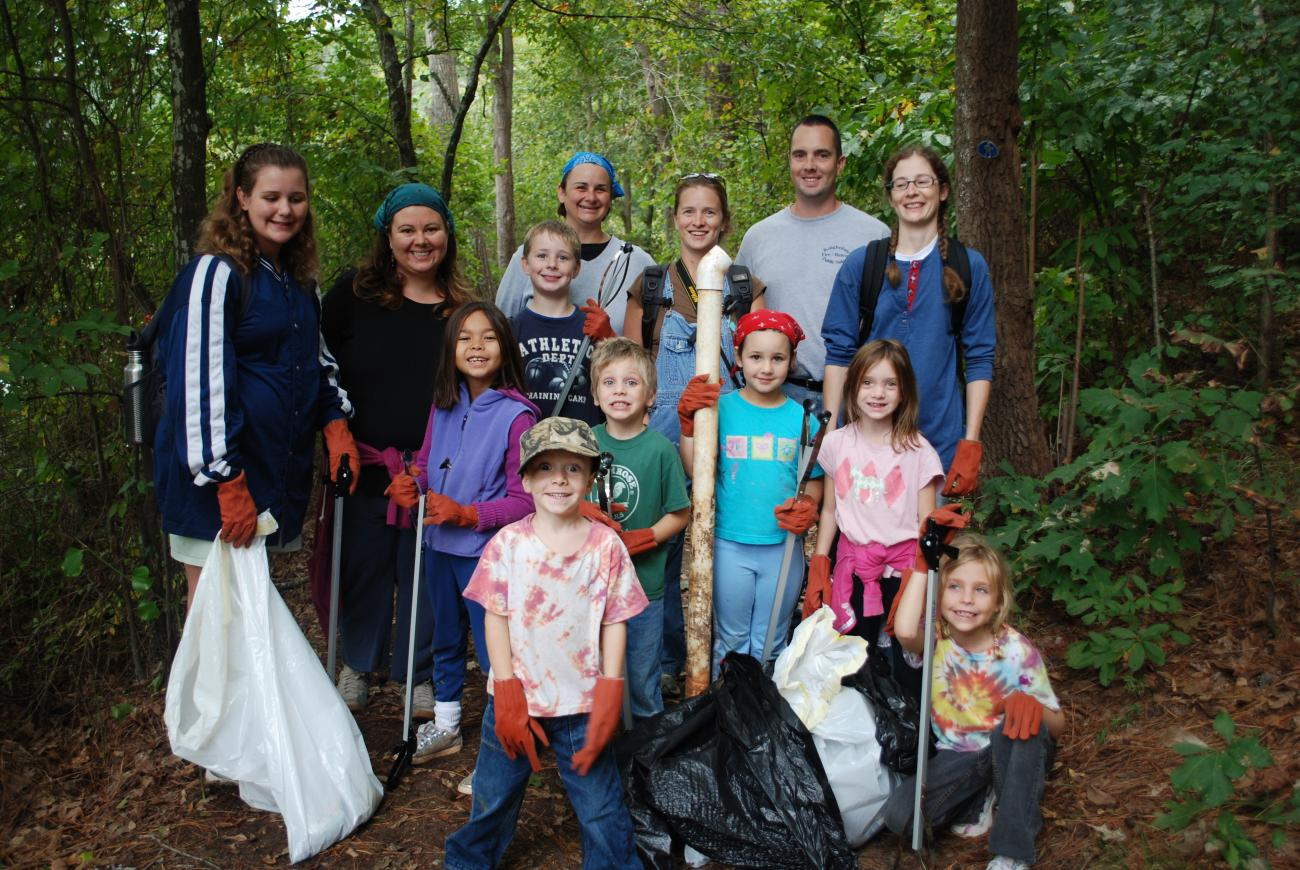 group of volunteers stand in forest with trash bags