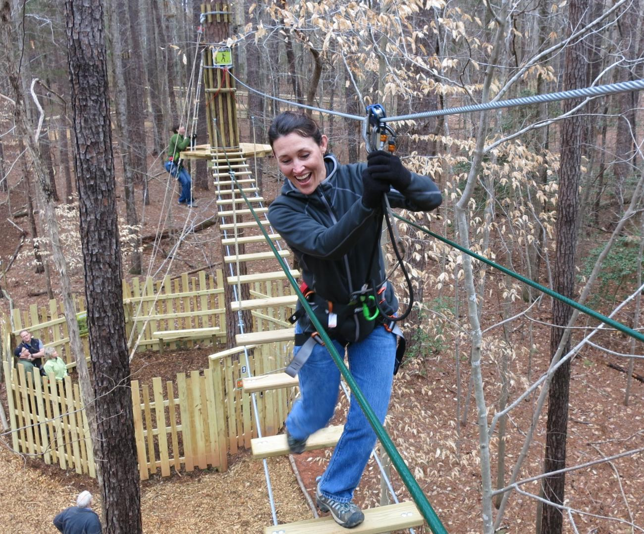 image of a woman making her way across an aerial rope obstacle 30 feet up in the trees