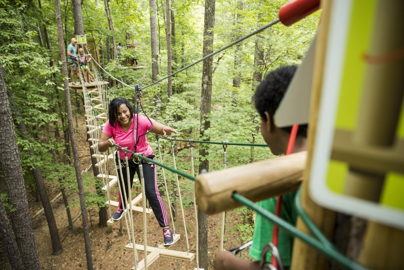 a woman in a hot pink top crossing an elevated obstacle on a Go Ape course