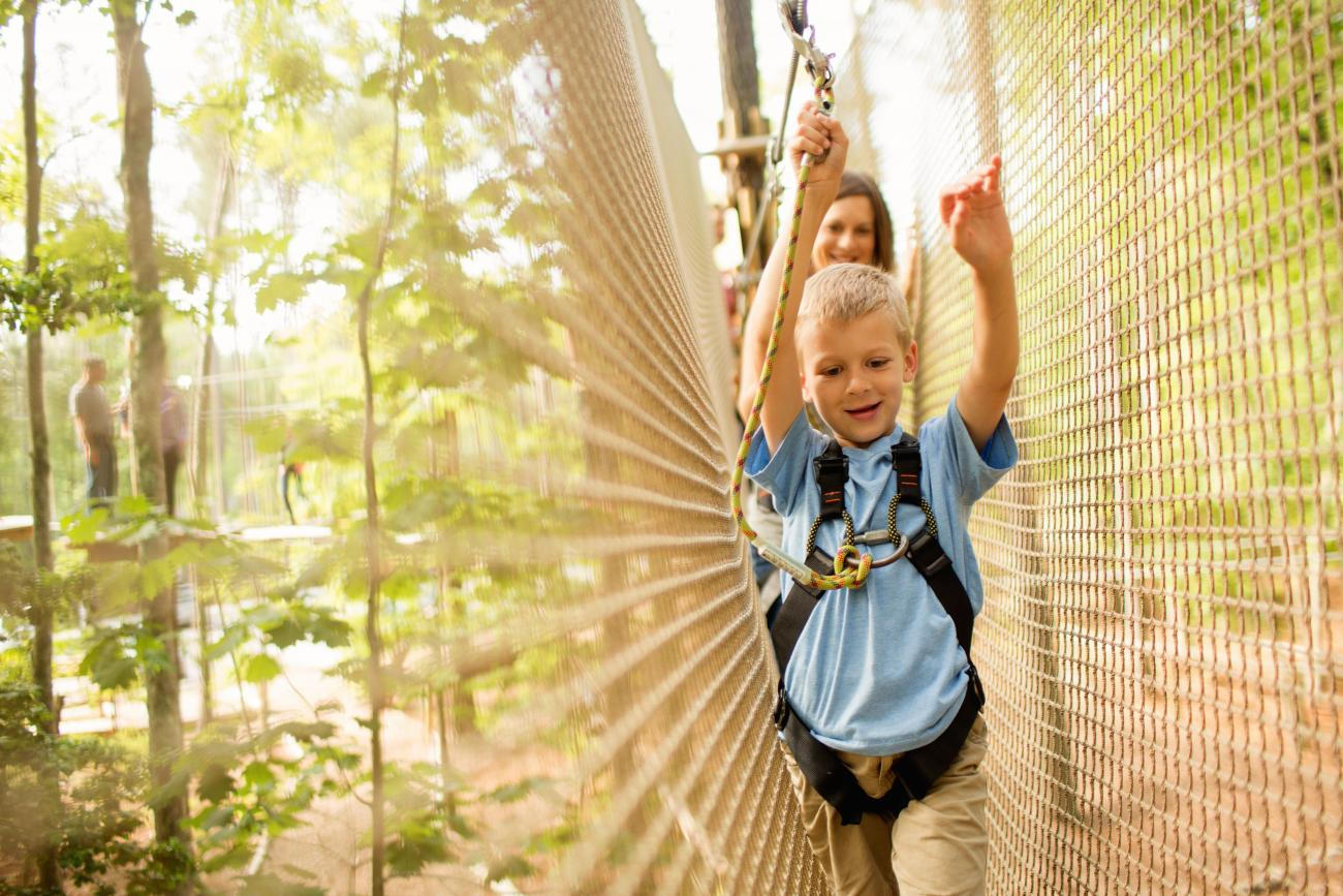 Young boy navigating an aerial obstacle with net walls on each side of him on the Go Ape Journeys course