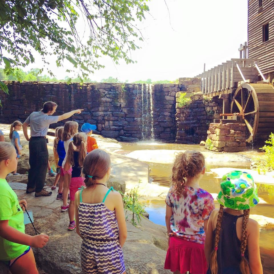 Group of children stand in front of mill dam and waterfall with mill building off to the side