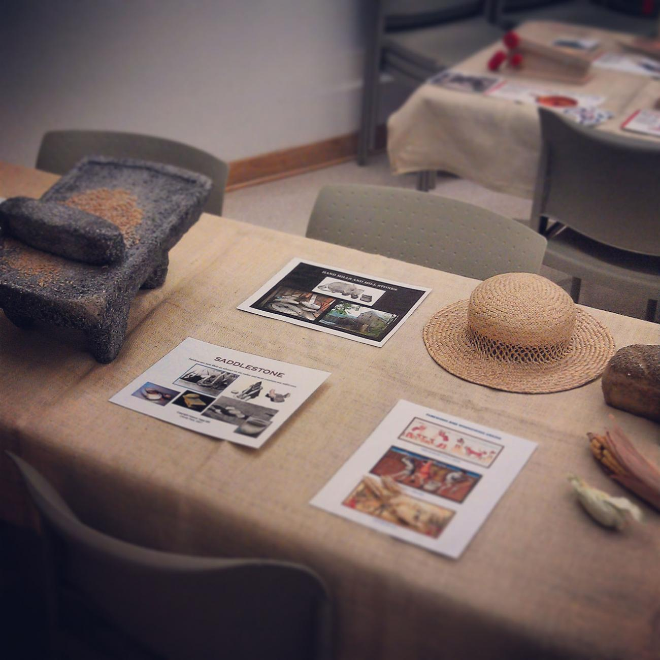 image of mortar and pestle, grain, and hat on table