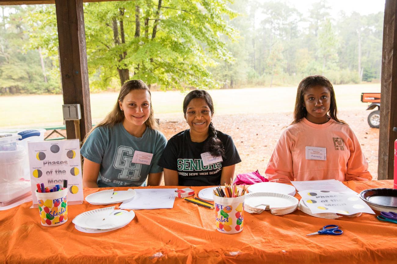 Photo of 3 volunteers assisting at a craft table at Haunting at Harris