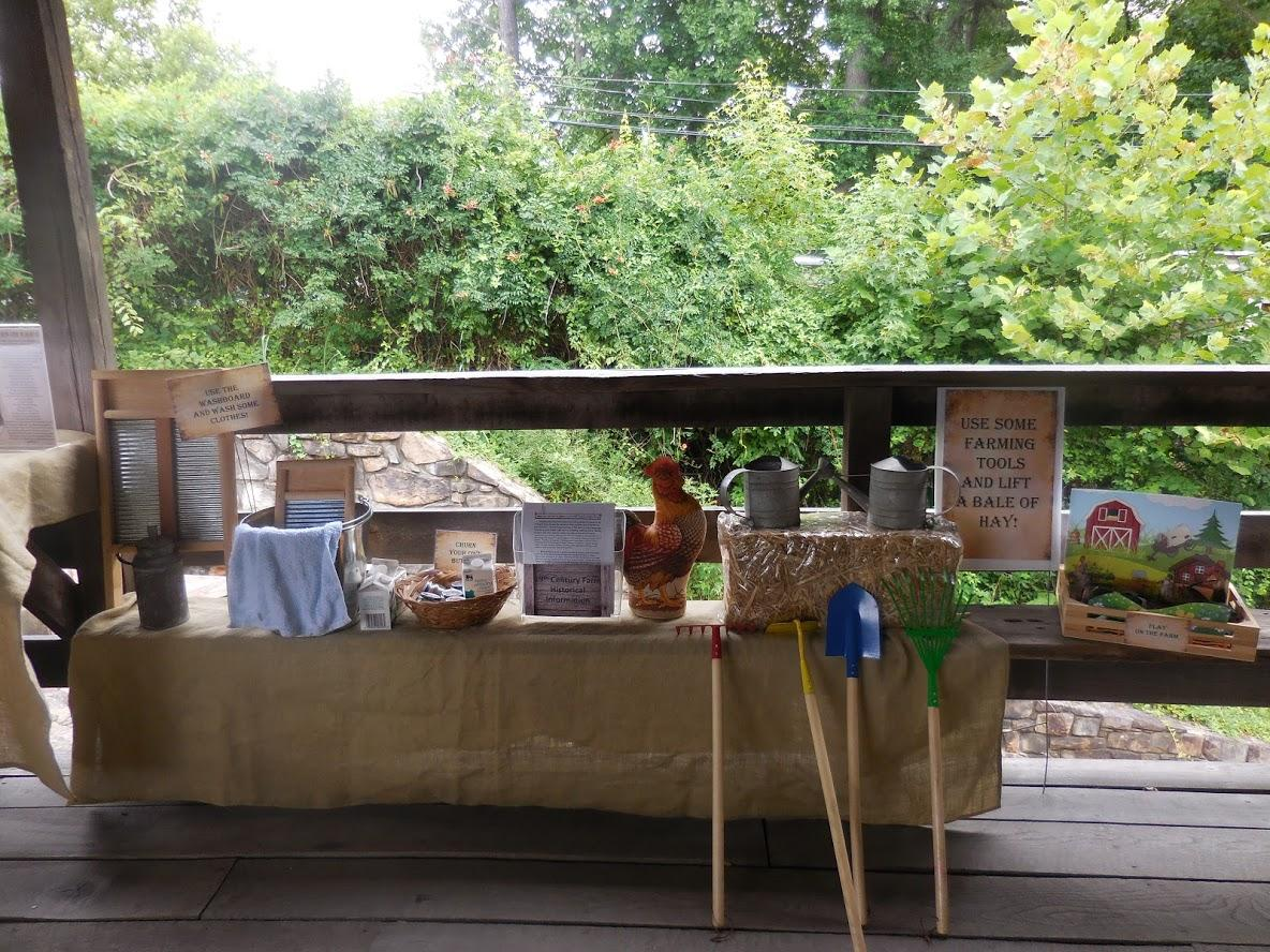 display table under old wooden mill with historical activities: washboards, hay bales ect