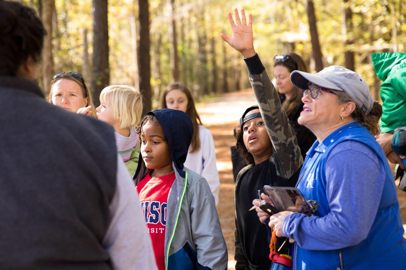 child raises hand at park program