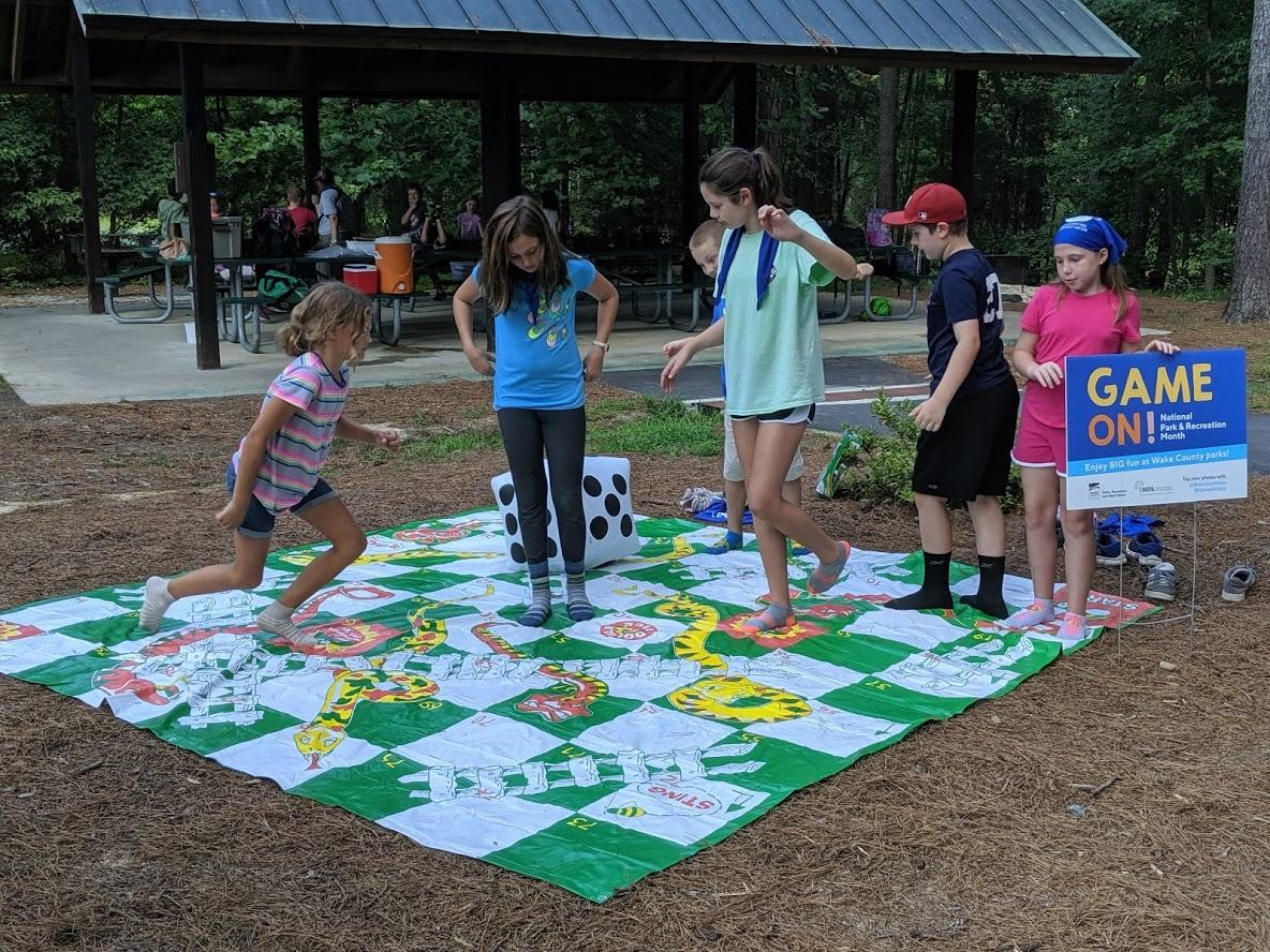 """Group of kids playing """"Snakes and Ladders"""" jumbo game on a large play mat"""
