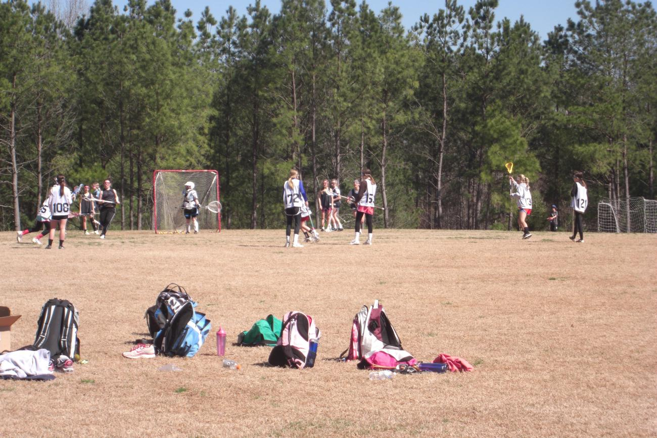Lacrosse players relaxing on the open play field.