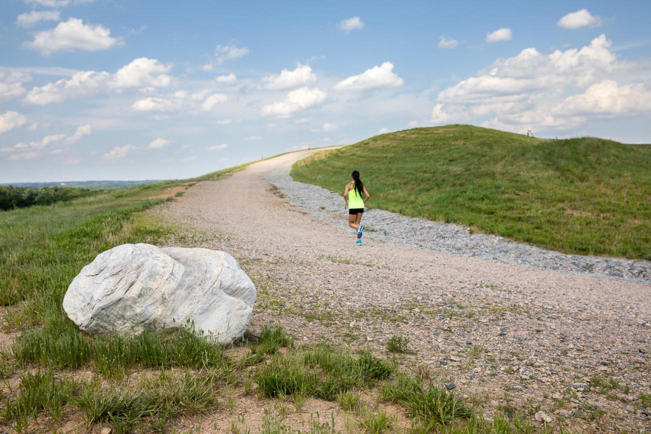 Woman running up the graveled Top of Hill Trail