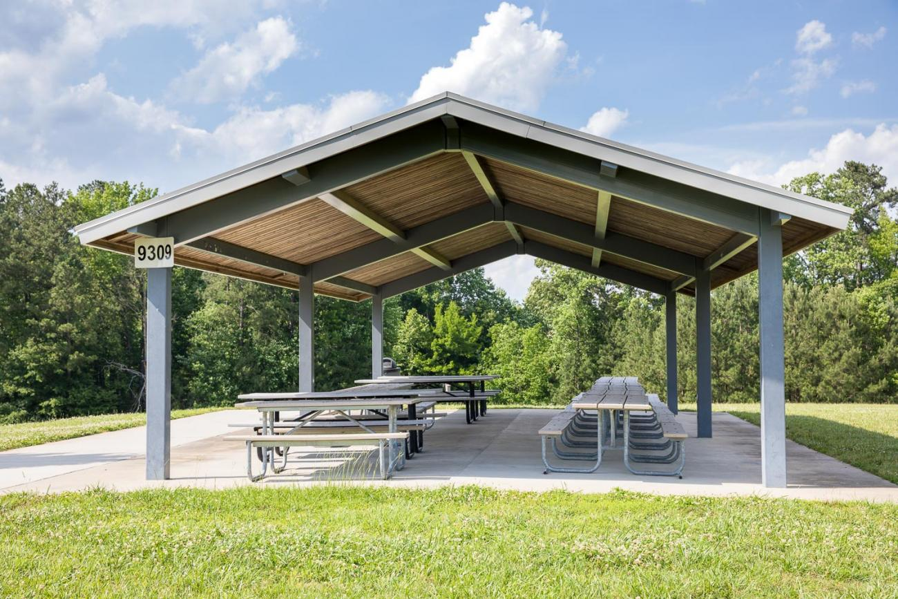 Large, open-sided picnic shelter on concrete slab surrounded by green grass.