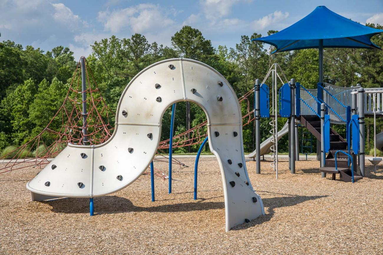 Climbing wall with play structure in the background