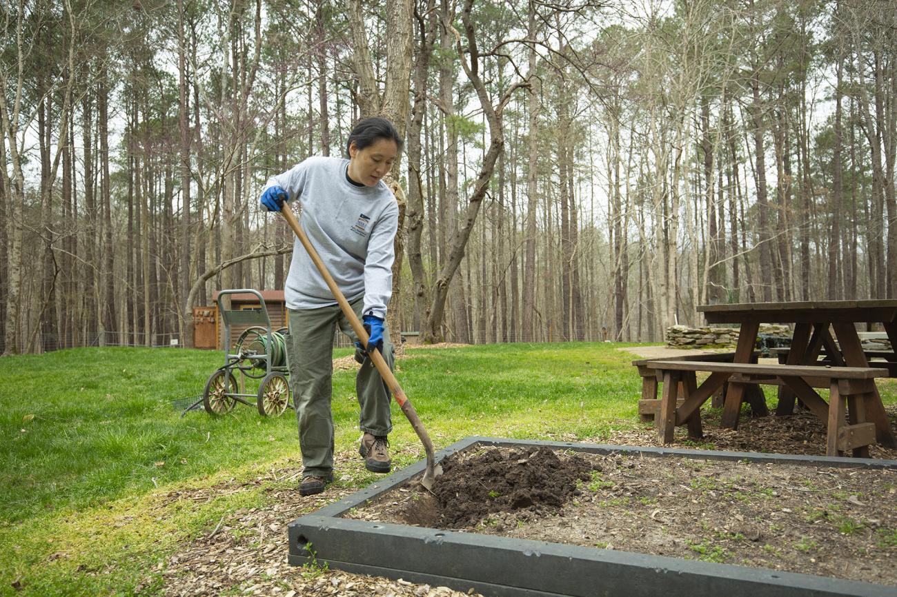 park employee working with shovel in garden