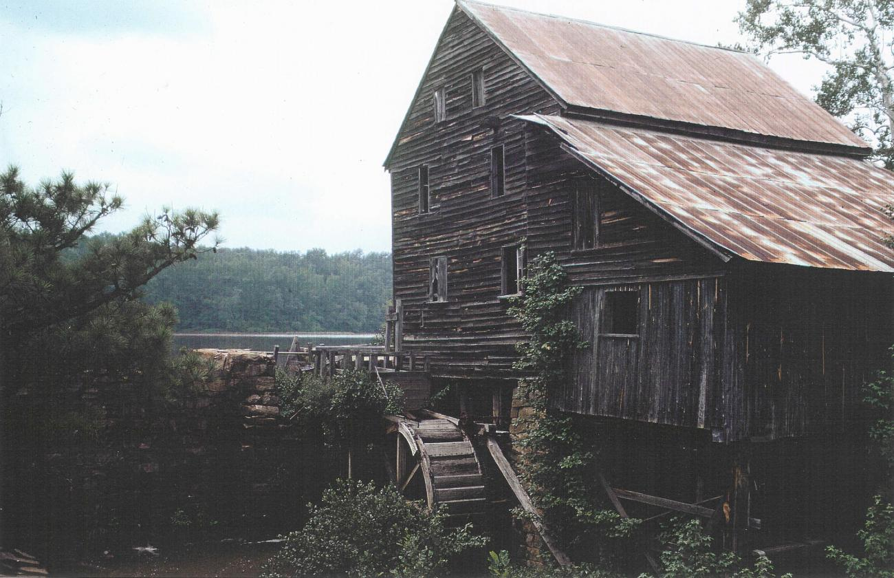Old color photo of the mill  before restoration, with ivy growing on the sides and parts falling apart
