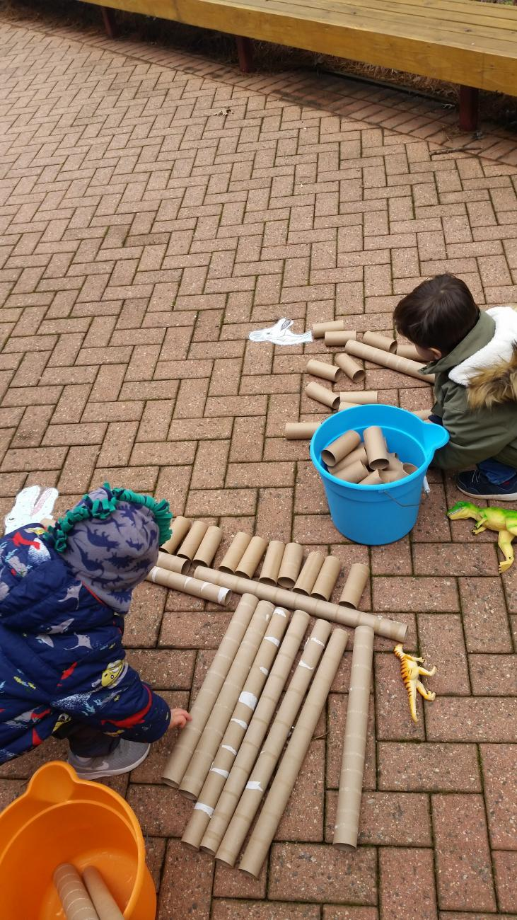 Preschool aged kids making a dinosaur skeleton out of cardboard tubes on the brick patio in front of the Education Center