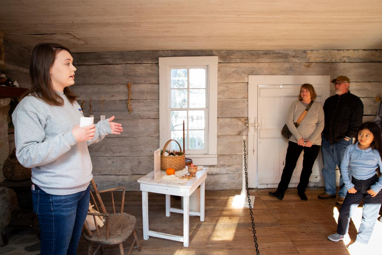 Staff member delivering a public tour to a group of visitors inside the 1825 detached kitchen