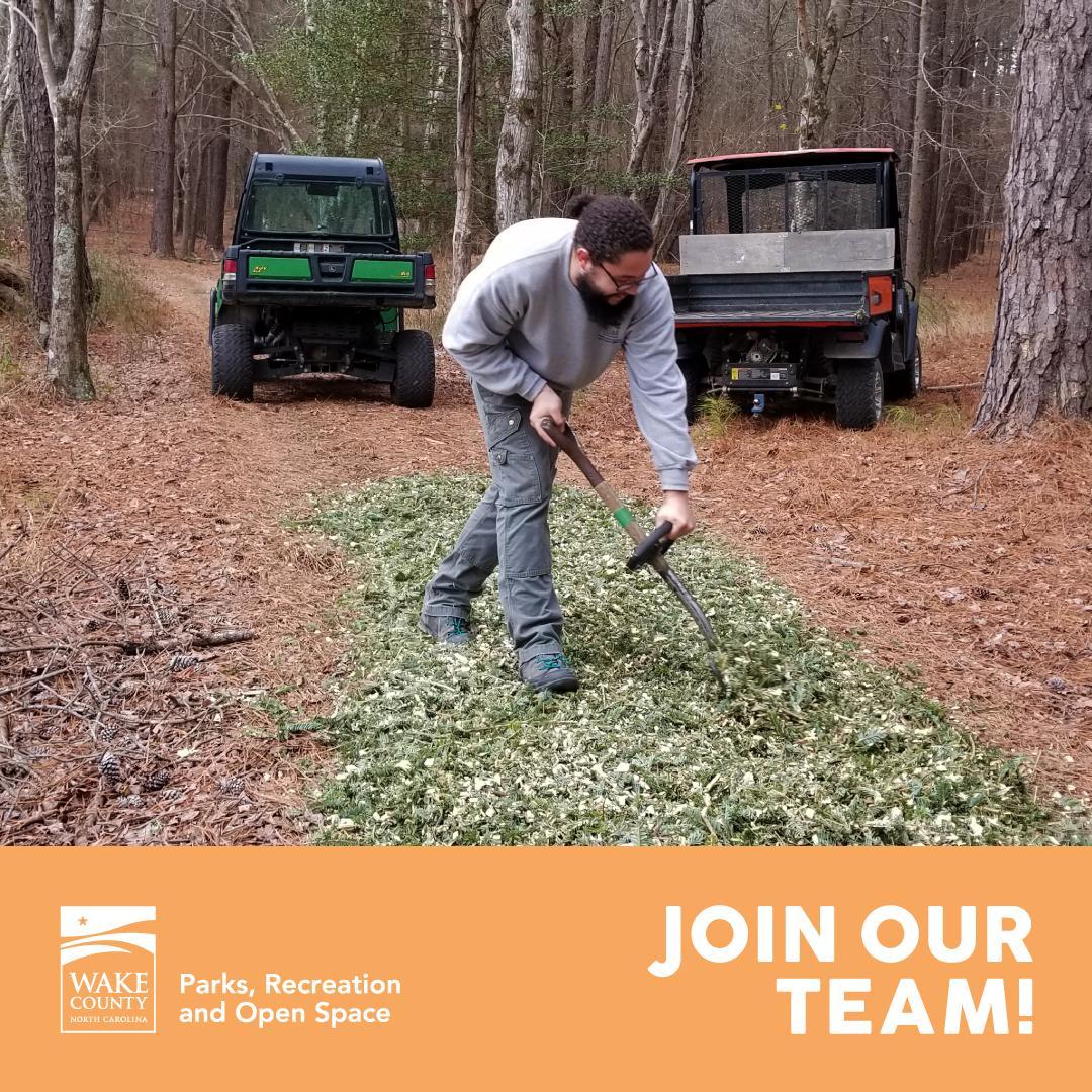 Park staff spreading mulch on a trail.
