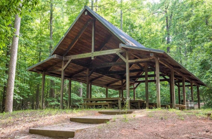 view of large wooden shelter in the woods