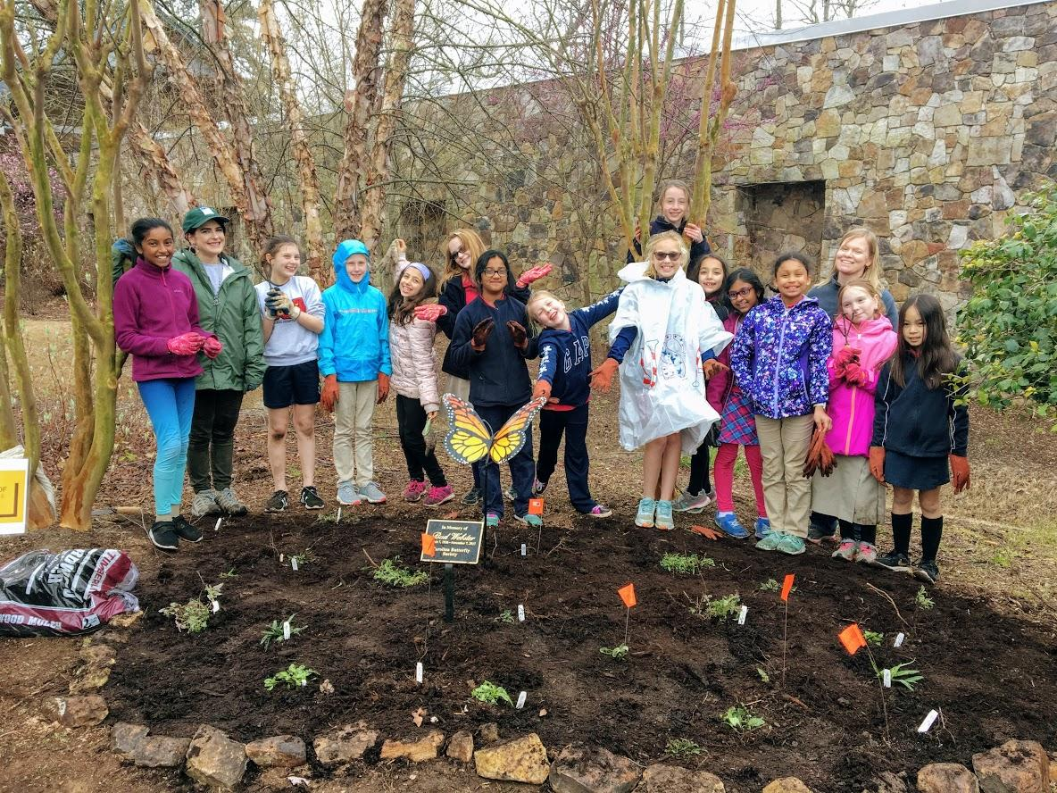educator stands with group of girl scouts around a new flower bed with freshly planted flowers