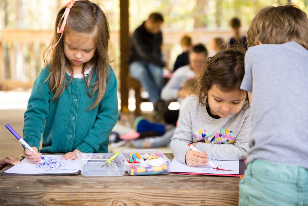 two girls color a craft together on a wooden bench