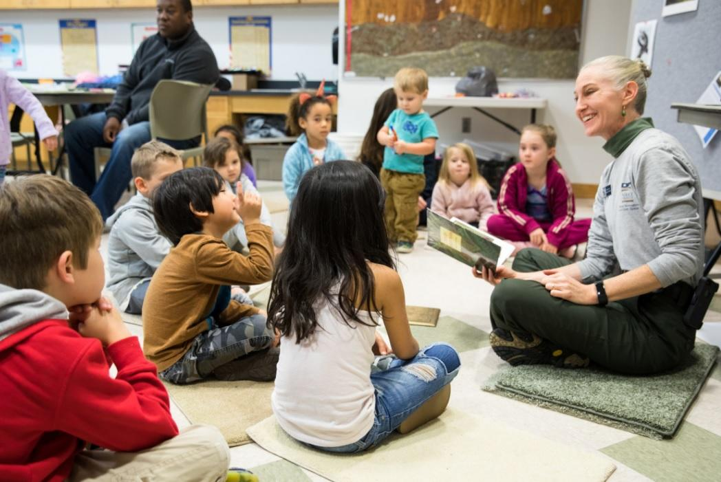 Educator sits on floor with group of children in classroom during storytime