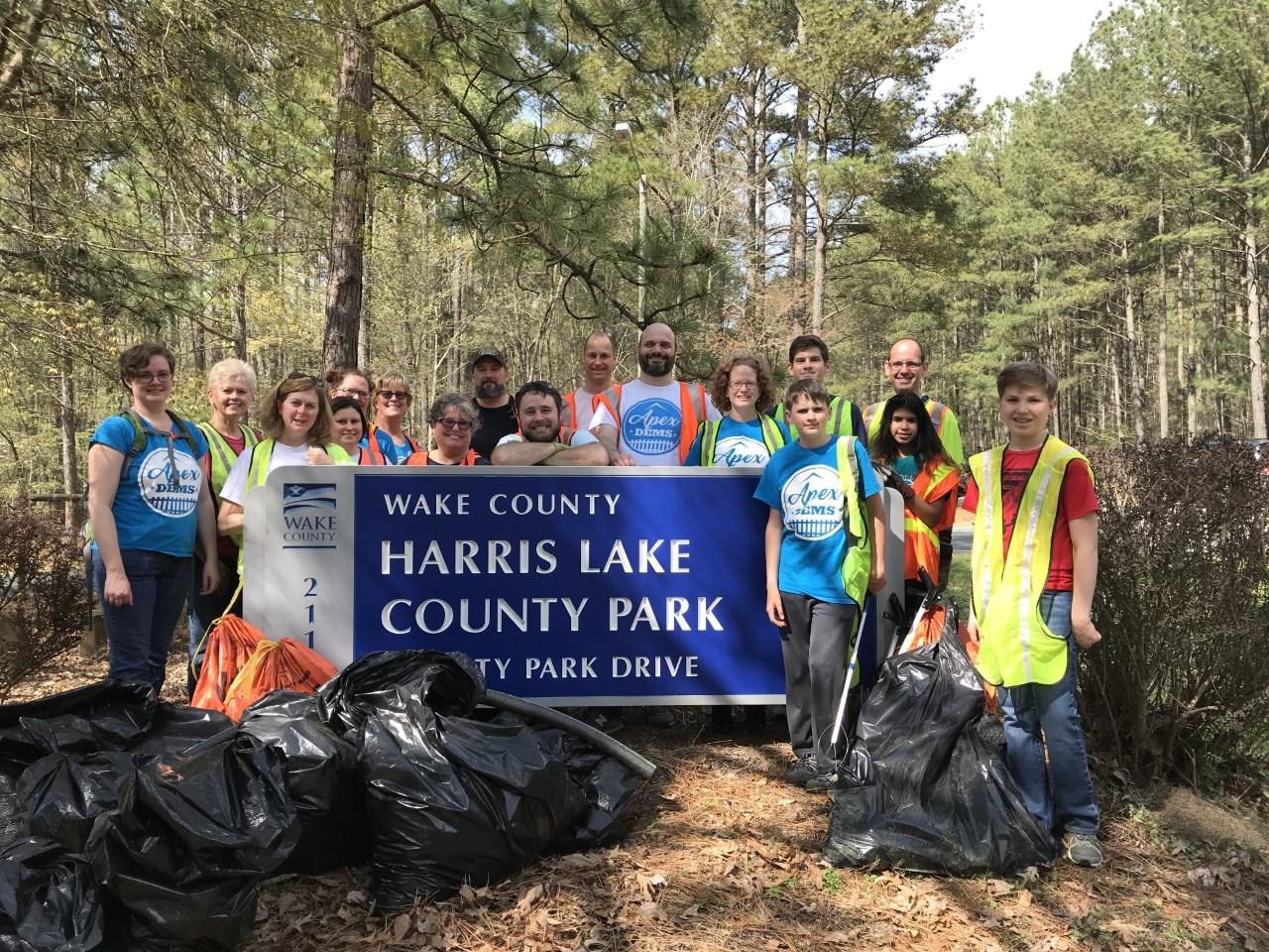 Photo of group of volunteers standing at the park entrance with collected bags of trash and debris