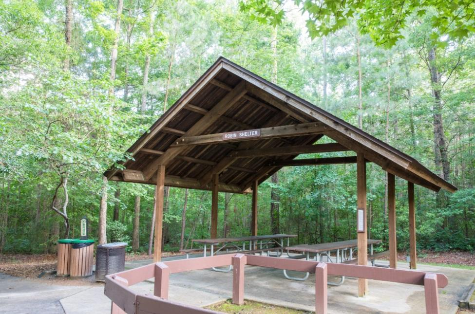 View of the parks smallest wooden picnic shelter with picnic tables