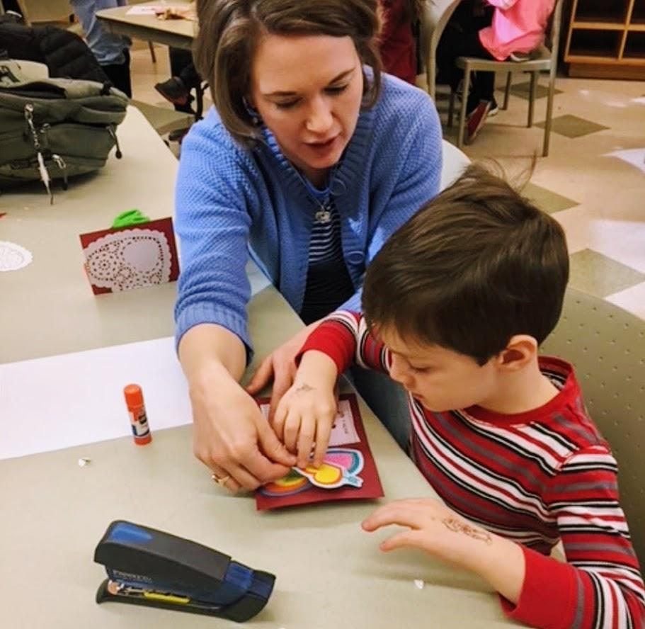 Mother and child work on valentine craft inside classroom during historical valentines day program