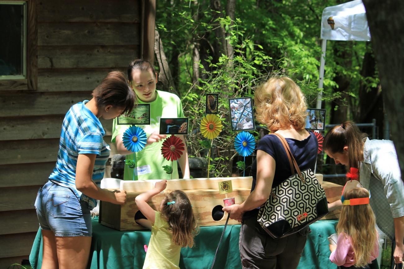 Older girl scout staffing an educational activity booth at Songbird Celebration