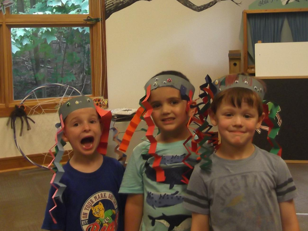 3 smiling young children with paper spider craft hats on their heads