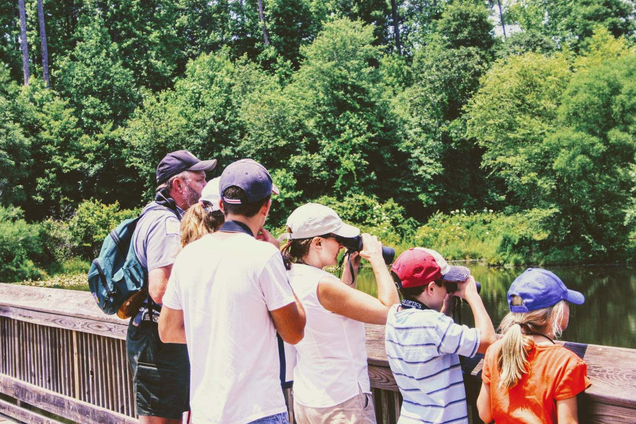 group of visitors stand together using binoculars looking over at wetlands from wooden boardwalk