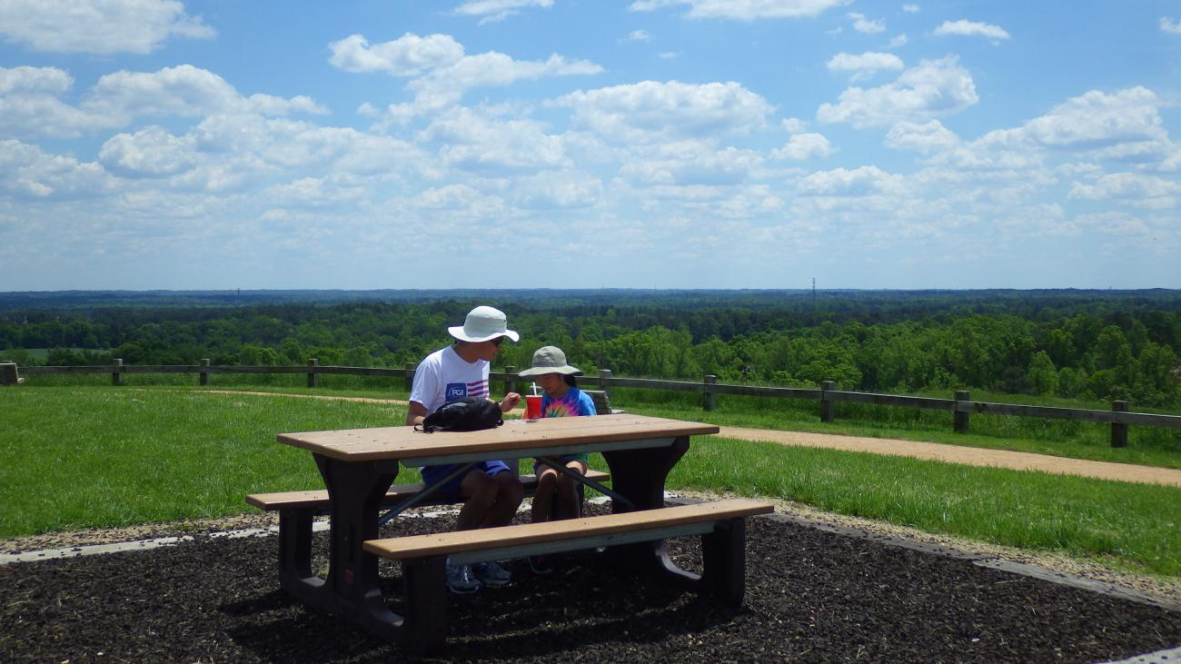 Father and daughter picnicking on top of big hill.