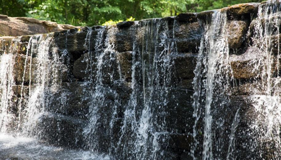 water flowing over stone mill dam