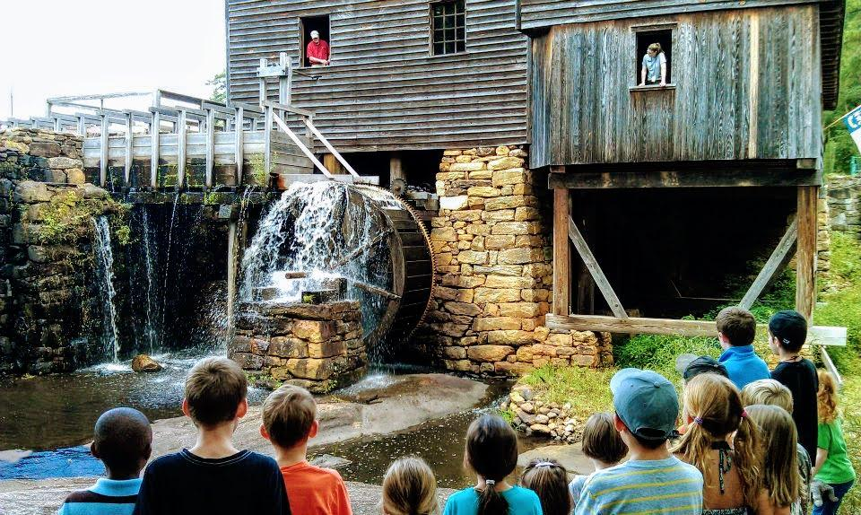 children watch mills waterwheel move by waterfall and dam