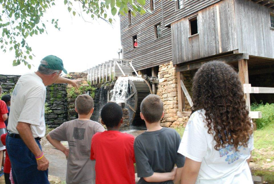 Group of school children stand outside old wooden mill building and waterfall