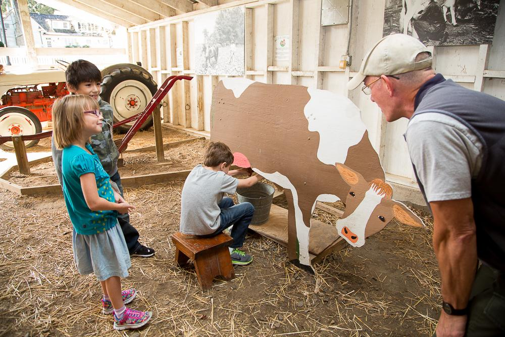 Kids in the barn using the milking interactive display