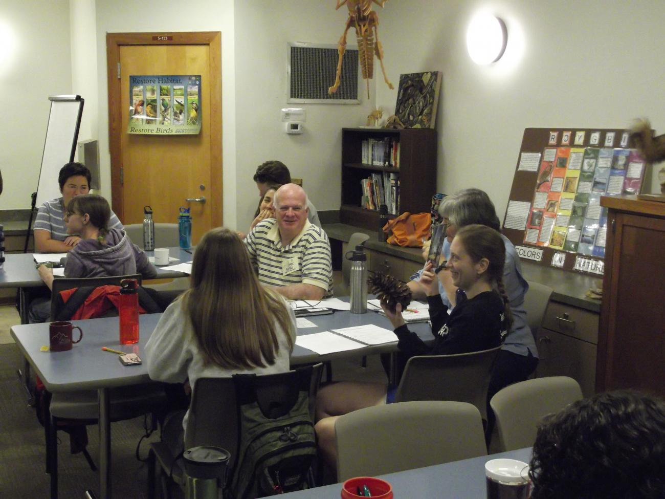 Adult workshop participants participating in a small group discussion inside a classroom in the Blue Jay Center for Environmental Education