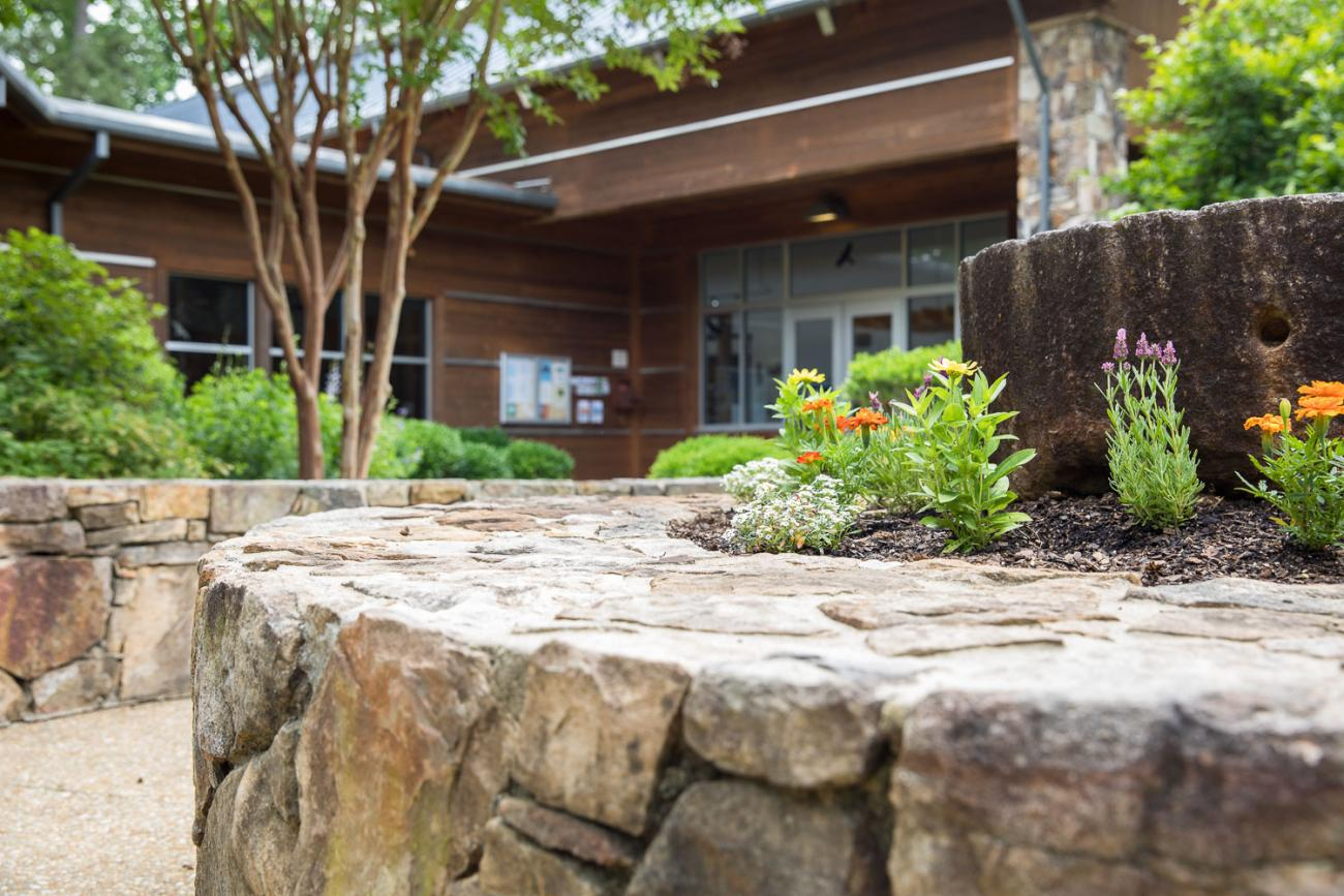 view of stone building with mill stone flower bed in front with paved stone path