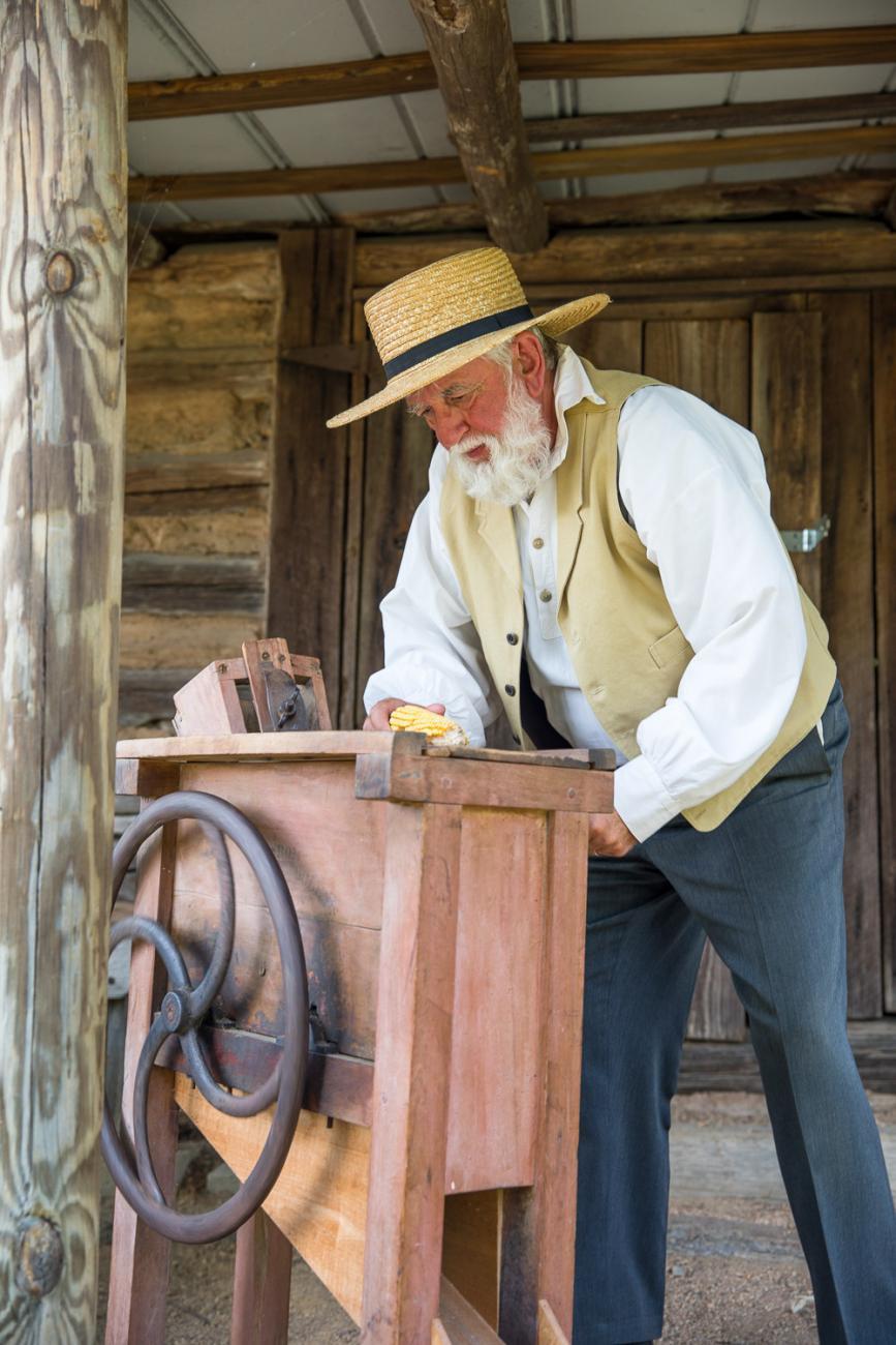 Costumed interpreter grinds corn inside of historic mill building