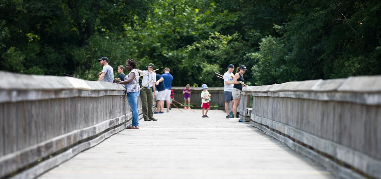 programmer teaches on wooden pond boardwalk while visitors fish with cane poles