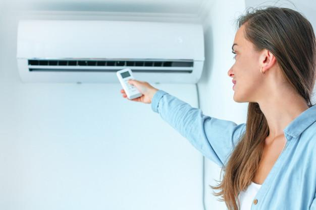 Woman controlling the air conditioner.