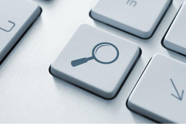close-up of a keyboard with a magnifying glass on one of the keys