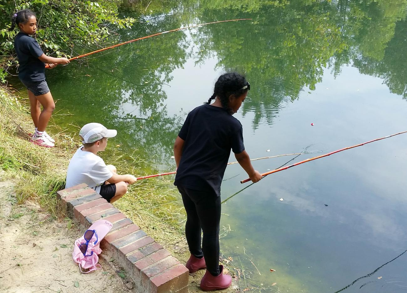 three children fishing with cane poles at the pond at Oak View