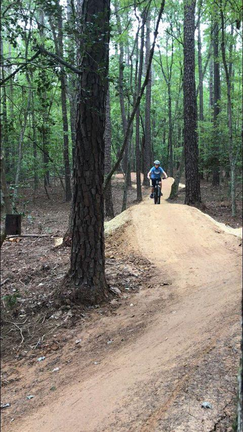 Photo of a person on a mountain bike using the Flow Trail found on the advanced section of the Hog Run mountain bike trail