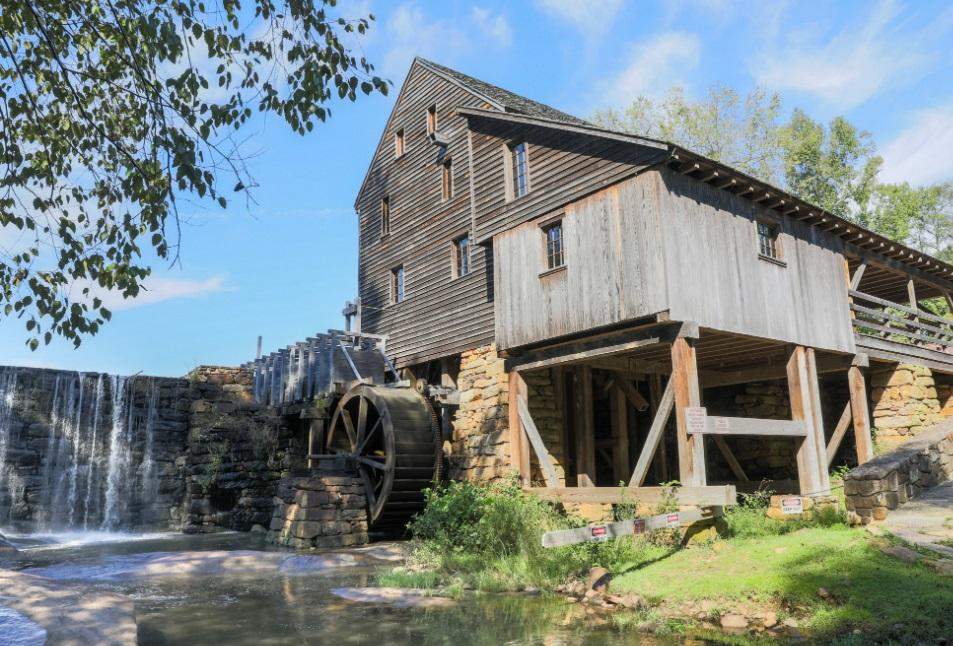 View of old wooden mill building with water flowing over dam