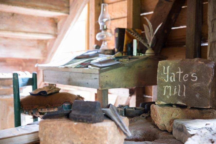 old desk with feather quill and rock that says yates mill inside old mill building