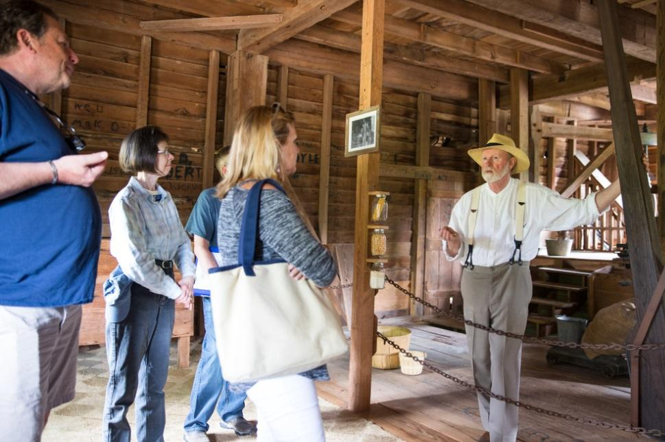 Volunteer speaks with tour participants inside of old mill